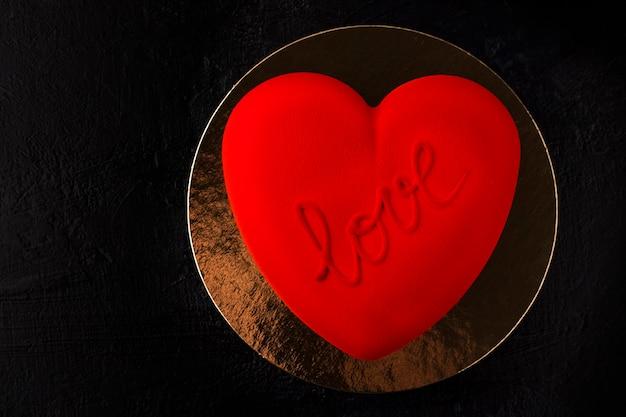 Herzförmiger kuchen aus rotem samt mit der aufschrift liebe auf goldenem substrat und schwarzem hintergrund. konzept für valentinstag, geburtstag. platz kopieren