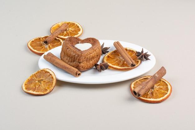 Herzförmiger kuchen mit orangenscheiben, nelken und zimt auf weißem teller