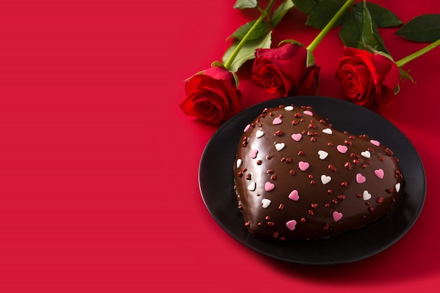 Herzförmiger kuchen und rote rose zum valentinstag