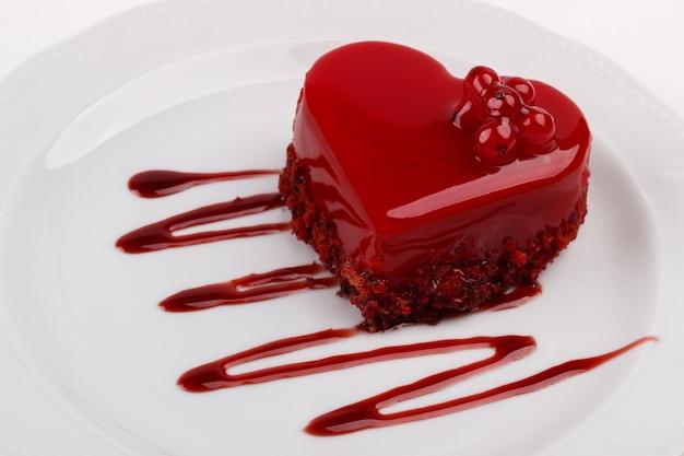 Herzförmiger kuchen verziert mit roter johannisbeere