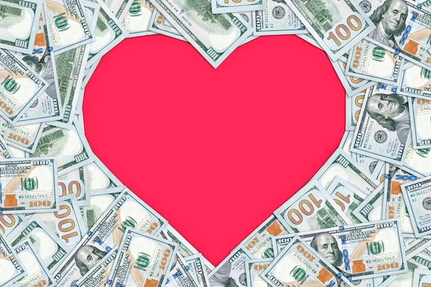 Herzförmiger leerer rahmen mit vielen 100-dollar-banknoten einzeln auf rosa. valentinstag. 14. februar. ein leeres formular für design und text. platz kopieren