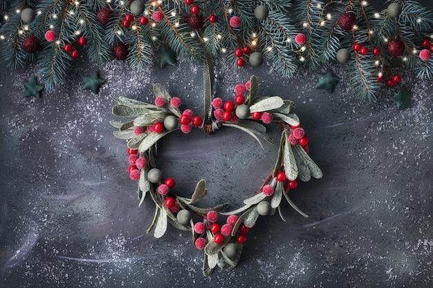 Herzförmiger mistelweihnachtskranz und festliche girlande aus tannenzweigen, gefrorenen beeren und schmuckstücken
