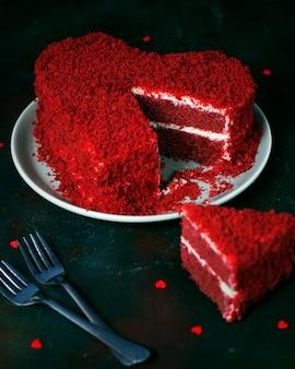 Herzförmiger roter samtkuchen auf dunkelheit