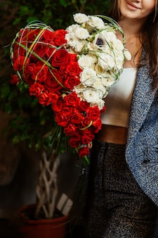 Herzförmiger strauß aus weißen und roten rosen