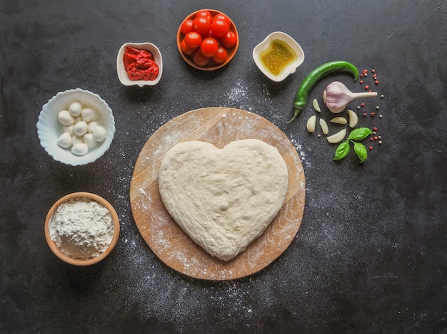 Herzförmiger teig und eine reihe von zutaten für pizza auf einem schwarzen tisch. der blick von oben