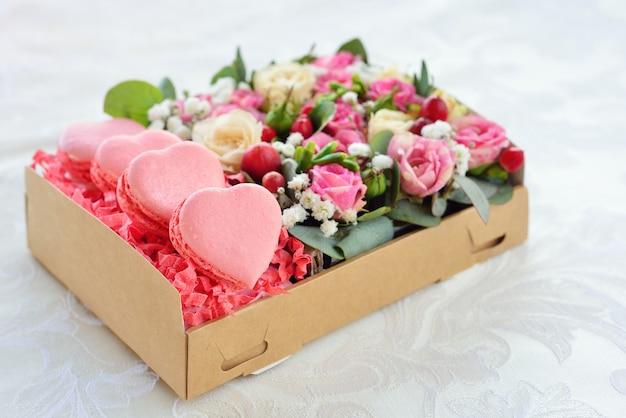 Herzförmiger valentinstag der französischen makrone, die schachtel mit blumen, rosa rosen, hintergrund für karte