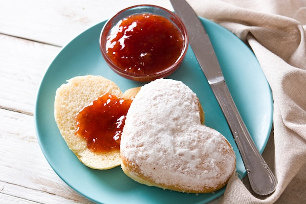 Herzförmiges brötchen des valentinstagfrühstücks und beerenmarmelade nah oben
