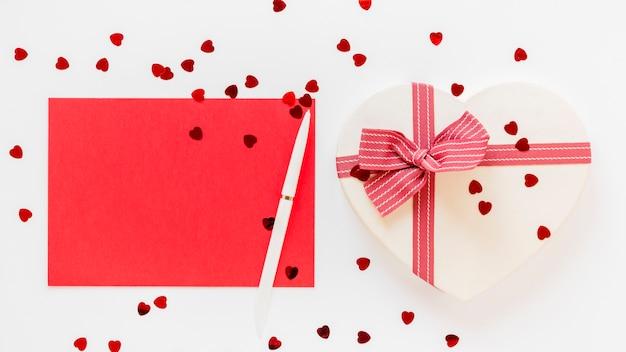 Herzförmiges geschenk mit stift und papier zum valentinstag