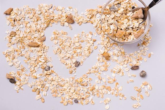 Herzförmiges natürliches köstliches müsli auf weiß. schöner ferienmorgen.
