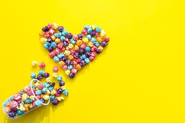 Herzform aus farbigem popcorn flach lag auf gelbem hintergrund