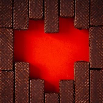 Herzform aus schokoladenwaffeln an roter wand. liebeskonzept. flach liegen.