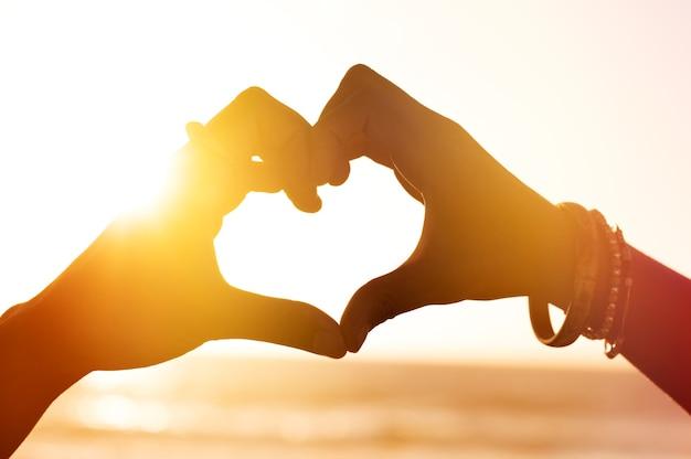 Herzform der hände gegen meer während des sonnenuntergangs