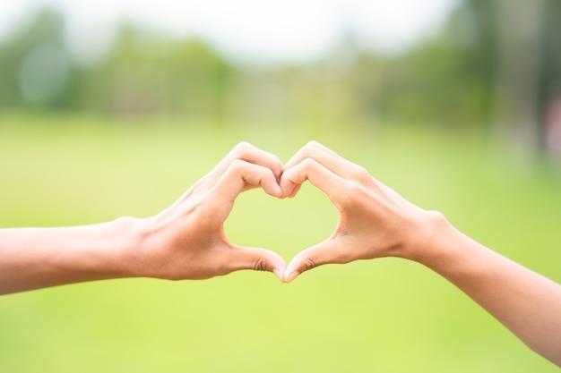 Herzform der hand auf unscharfem hintergrund