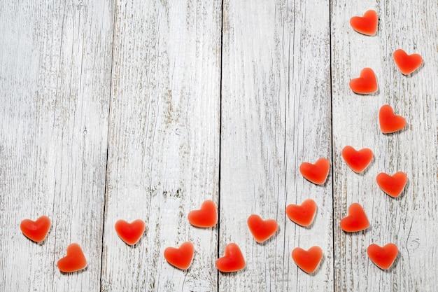 Herzform der roten süßigkeit der süßen marmelade auf weißem holztisch, valentinstagkomposition mit copyspace.