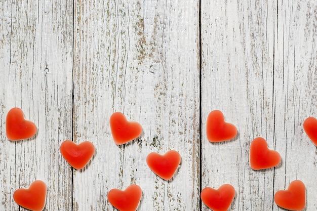 Herzform der roten süßigkeit der süßen marmelade auf weißem holztisch