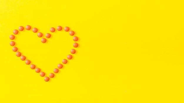 Herzform gemacht mit pillen auf gelbem hintergrund