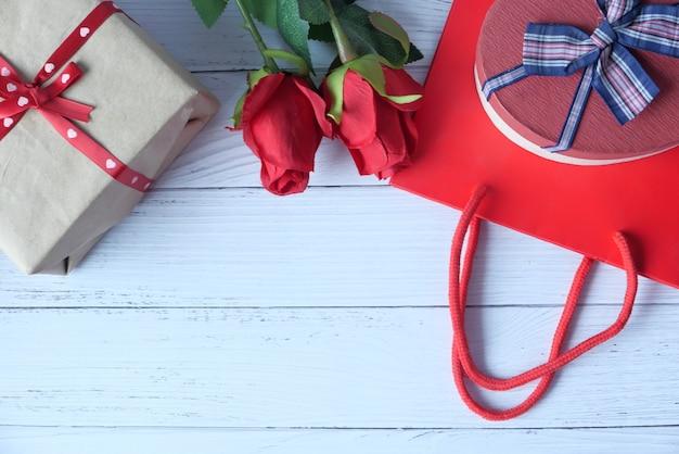 Herzform geschenkbox einkaufstasche und rosenblume auf tisch
