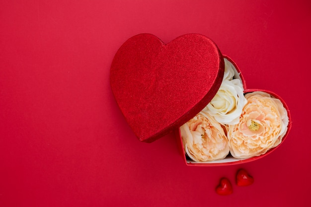 Herzform-geschenkbox mit blumen auf rotem backgroun. valentinstagspott oben mit exemplarplatz.