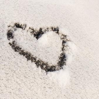 Herzform gezeichnet auf schnee bedeckte fenster. valentinstag-konzept