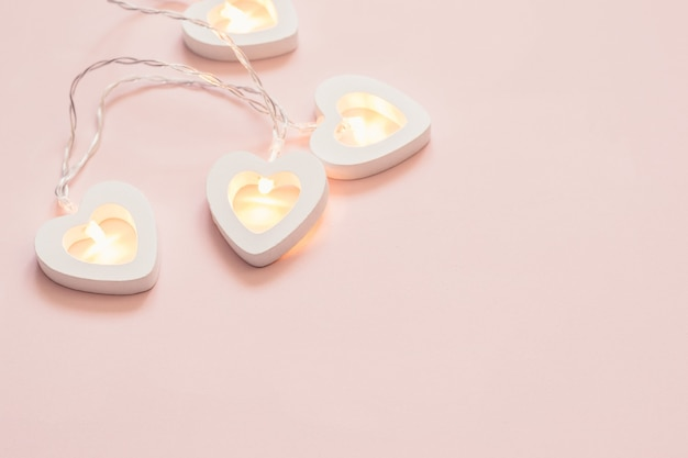 Herzform girlande auf rosa pastellhintergrund. minimale dekoration zum valentinstag oder zur hochzeitsfeier.