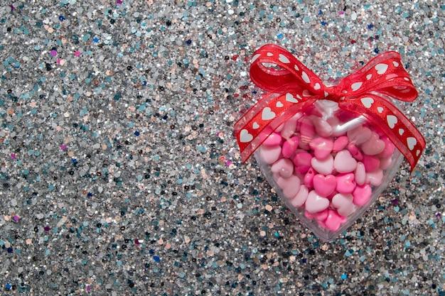 Herzform mit bogen auf glänzendem glitzerhintergrund für valentinstag mit kopienraum