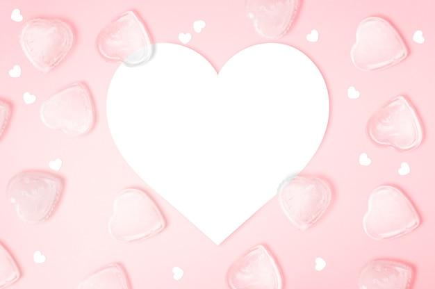 Herzform-notizpapier mit herzeiswürfeln auf rosa hintergrund mit kopienraum, glücklicher valentinstag, muttertag, flache lage, draufsicht