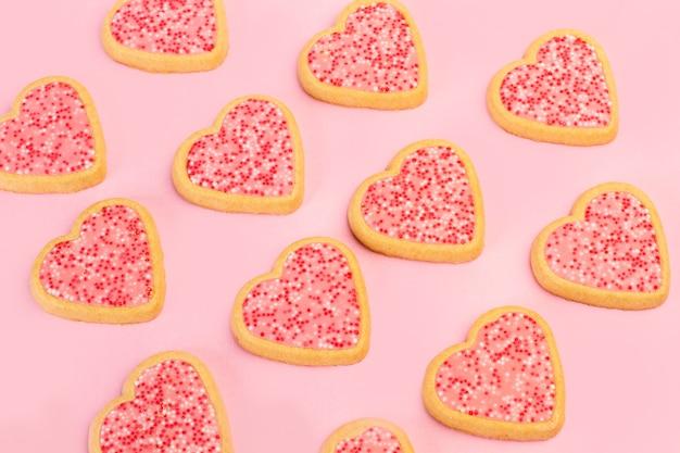 Herzform rosa kekse auf einem rosa hintergrund