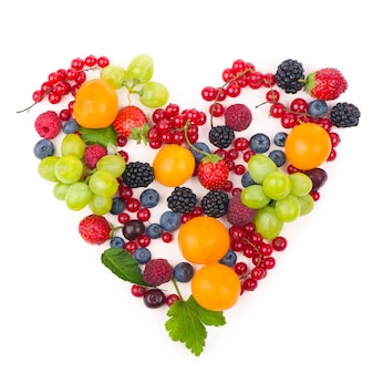 Herzform sortierte beerenfrüchte auf weißer oberfläche. schwarz-blaues und rotes essen. gemischte beeren mit kopierraum für text. verschiedene frische sommerbeeren. beeren in herzform isoliert auf einem weiß.