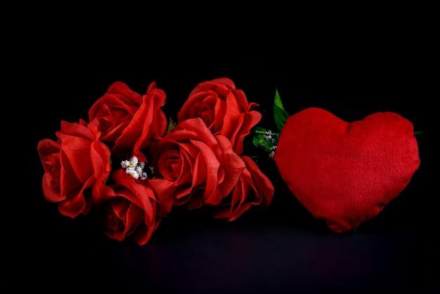 Herzform und rotrose auf schwarzem hintergrund