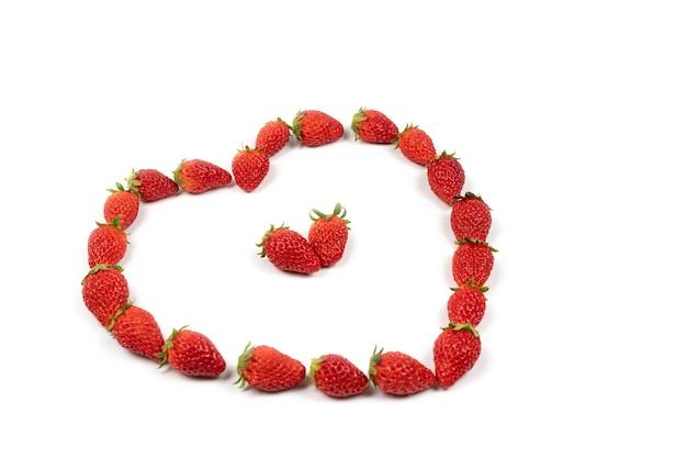 Herzform von erdbeeren in der linie. rote frische erdbeere