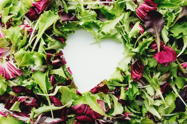 Herzform von grünen und lila salatblättern mischen hintergrund. weißer tisch