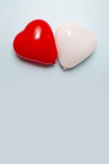 Herzform zwei luftballons auf blauem oberflächenkopierraum