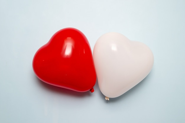 Herzform zwei luftballons auf blauer oberfläche