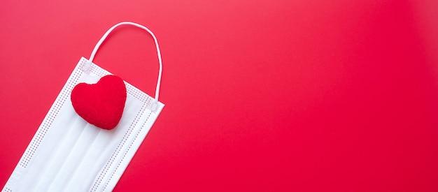Herzformdekoration und medizinische gesichtsmaske auf rotem hintergrund gegen coronavirus-krankheit-infektion