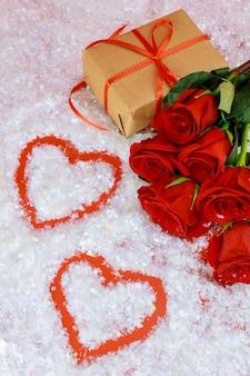Herzformen auf funkelndem schnee und schönen roten rosen mit geschenkbox. muttertag oder valentinstag.