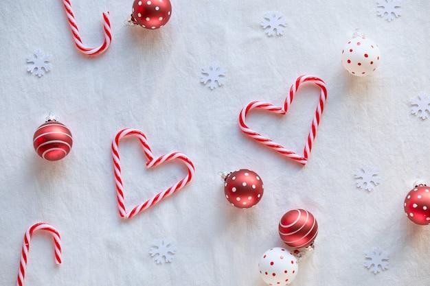 Herzformen aus zuckerstangen, rot-weiß gefleckte schmuckstücke auf weißem textil. hand halten herz.