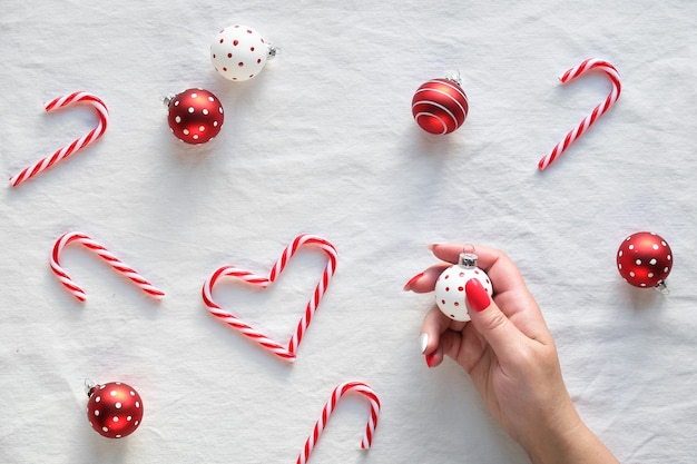 Herzformen aus zuckerstangen, roten und weißen schmuckstücken mit punkten auf weißem textil. hand halten