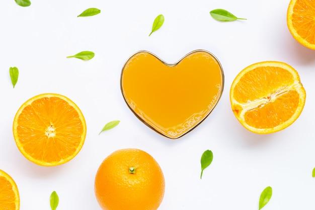 Herzformglas frischer orangensaft mit orange frucht auf weißem hintergrund.