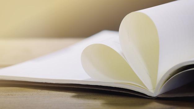 Herzformpapierbuch auf hölzerner tabelle