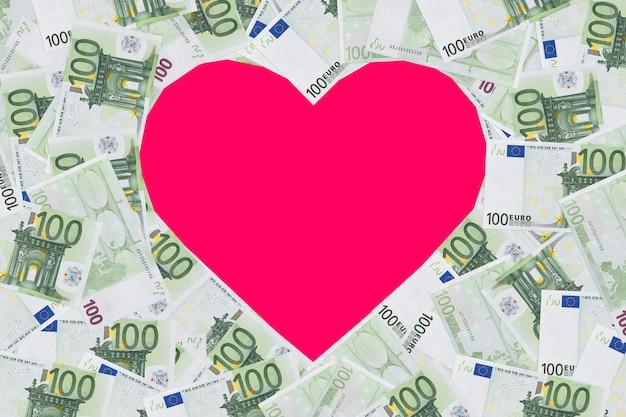 Herzformschild mit 100 euro-banknoten. valentinsgrußkonzepthintergrund. herz von banknoten in 100 euro. platz für text. platz kopieren. das formular, leer für design. exemplar.