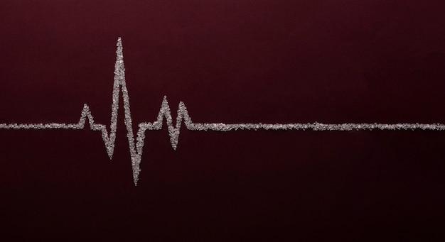 Herzfrequenzdiagramm unter verwendung von weißem zucker auf rotem hintergrund