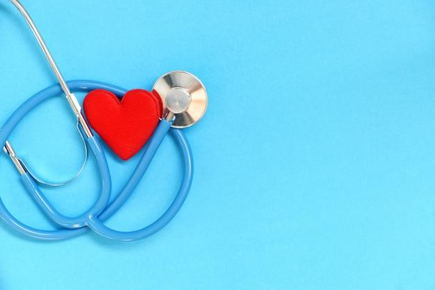 Herzgesundheit und rotes herz mit stethoskop auf blauer wand - weltherztag weltgesundheitstag oder welthypertonietag und krankenversicherungskonzept