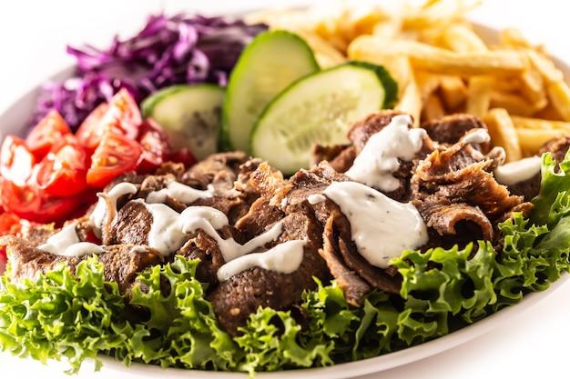 Herzhafter türkischer kalbskebab serviert mit frischem gemüse, salat, französischem feuer und einem köstlichen dip, mayonnaise.