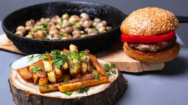 Herzhaftes leckeres rustikales mittagessen. pommes frites burger und champignon mit gebratenen pilzen aus gusseisen auf hölzernen untersetzern im wald.