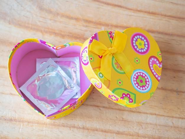 Herzkasten auf bretterboden mit kondomkonzept