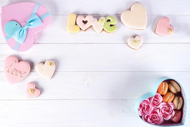 Herzkasten mit macarons und rose auf weißem hölzernem hintergrund, valentinstag