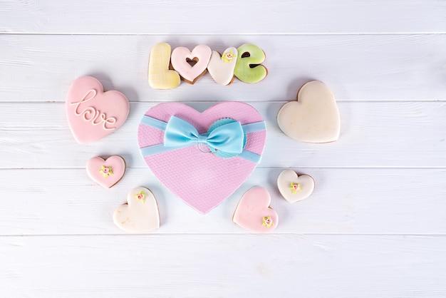 Herzkasten mit plätzchen und rose auf weißem hölzernem hintergrund, valentinstag
