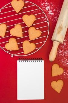 Herzkekse in der nähe von notizblock, nudelholz und grill