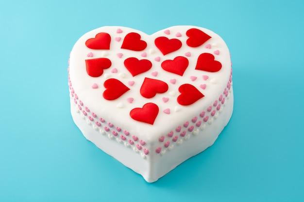 Herzkuchen für valentinstag, verziert mit zuckerherzen auf blauem hintergrund