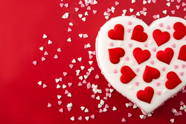 Herzkuchen für valentinstag, verziert mit zuckerherzen auf rotem hintergrund